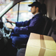 Download Delivery driver driving van with parcels on seat outside warehouse from PhotoDune