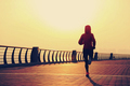 young fitness woman runner running at sunrise seaside