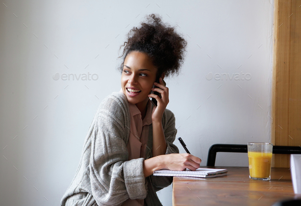 Female student working at home and talking on mobile phone - Stock Photo - Images