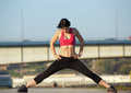 Athletic young woman stretching muscles outdoors