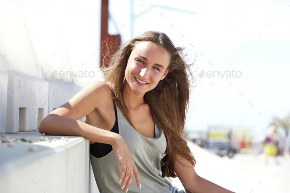 Happy young woman sitting outside - Stock Photo - Images