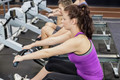 Fit woman on drawing machine at gym
