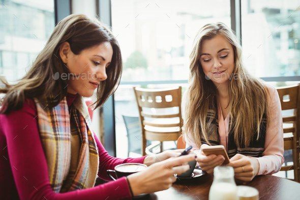 Friends using their smartphone in cafe - Stock Photo - Images
