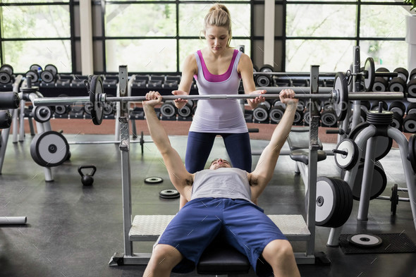 Trainer woman helping athletic man in gym - Stock Photo - Images
