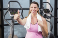 Happy pregnant woman showing thumb up at the gym