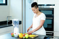 Portrait of pregnant woman in kitchen cutting fruits on chopping board