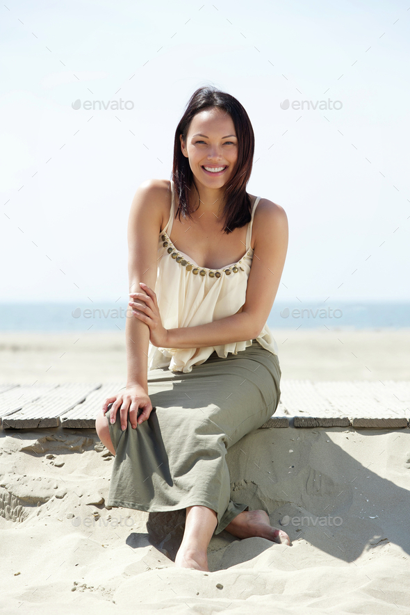 Cheerful young woman sitting at the beach - Stock Photo - Images