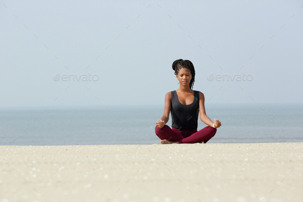 African woman sitting at beach in yoga pose - Stock Photo - Images