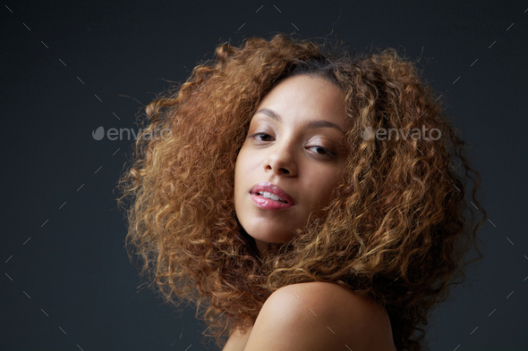 Beauty portrait of a pretty young woman with curly hair - Stock Photo - Images