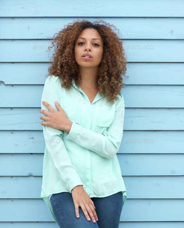 Female fashion model with curly hair standing outdoors - Stock Photo - Images