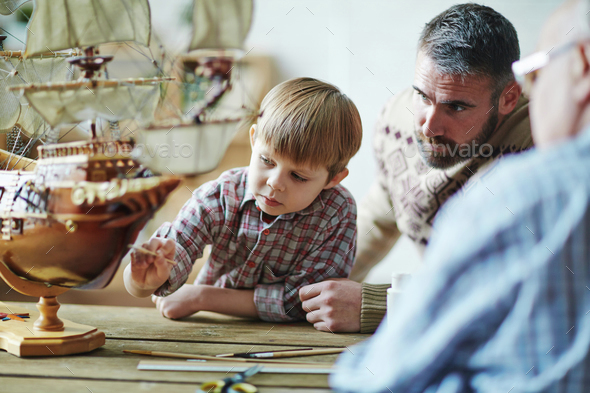 Painting toy ship with father - Stock Photo - Images