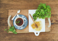 Cup of herbal tea with fresh mint and honey on wooden tray over rustic background. Top view.