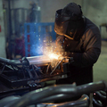 worker welding exhaust pipes pieces together - PhotoDune Item for Sale