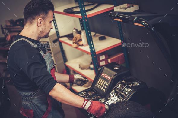 Professional car  mechanic balancing car wheel on balancer in au - Stock Photo - Images