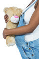 Pregnant woman holding a teddy bear on white background