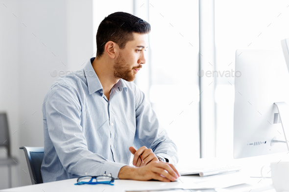Male office worker sitting at desk - Stock Photo - Images