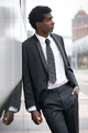 Portrait of a handsome young black man wearing a business suit in the city