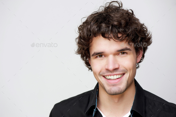 portrait of a handsome young man smiling - Stock Photo - Images