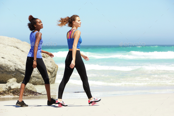 Two young sporty women walking on beach - Stock Photo - Images