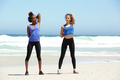 Two healthy young women stretching exercise at the beach