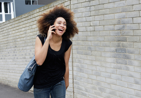 Young woman walking and laughing on mobile phone - Stock Photo - Images
