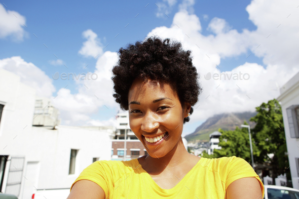 Happy young woman standing outdoors - Stock Photo - Images