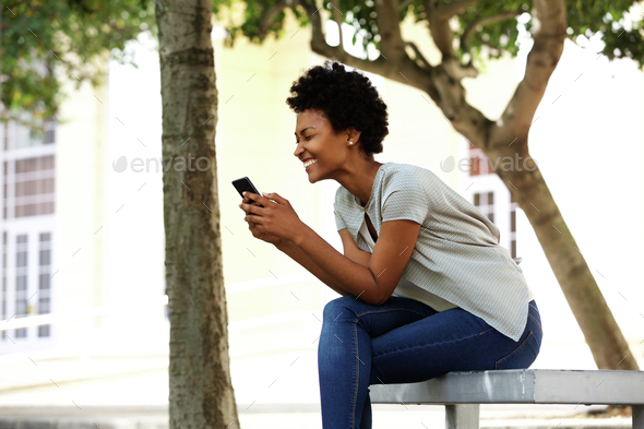 Cheerful young woman sitting on a bench reading text message - Stock Photo - Images