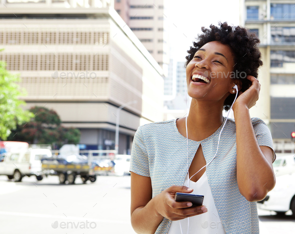 Smiling young woman listening music on headphones - Stock Photo - Images