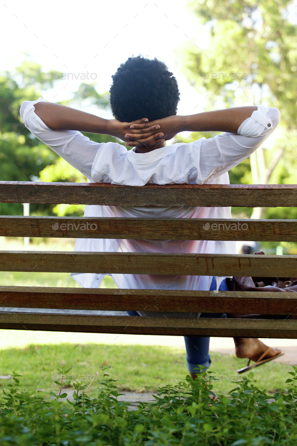 Relaxed Young Woman Sitting On A Park Bench Stock Photo By