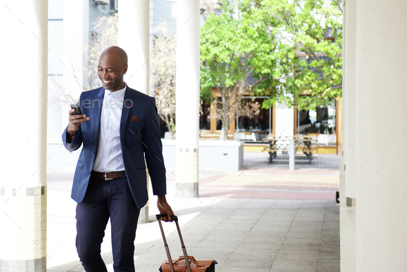 Businessman traveling with a bag and mobile phone - Stock Photo - Images