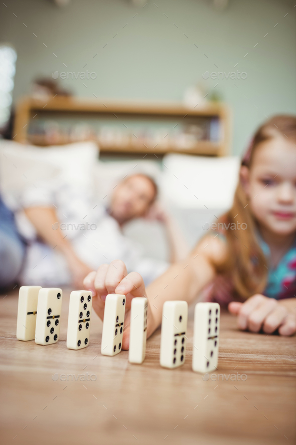 Close-up of girl arranging domino on hardwood floor at home - Stock Photo - Images
