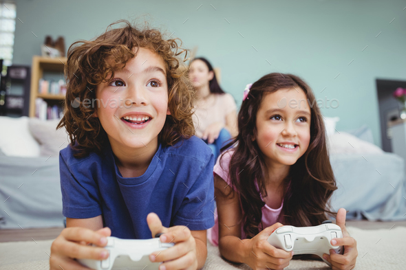 Close-up of happy siblings with controllers playing video game on carpet at home - Stock Photo - Images