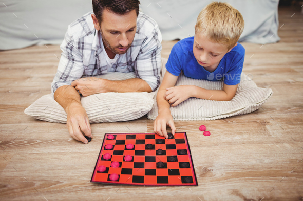 Father and son playing checker game while lying on hardwood floor at home - Stock Photo - Images
