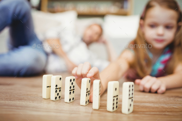 Close-up of girl arranging domino on floor at home - Stock Photo - Images
