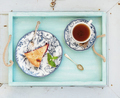 Piece of double crust plum pie and black tea in vintage porcelain cup