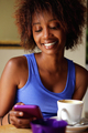 Smiling young african woman using cellphone at cafe