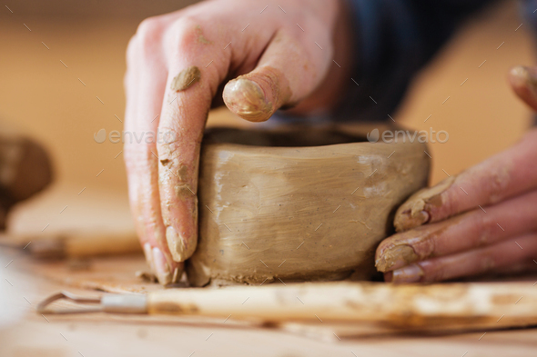 Earthen jar making by hands of woman potter in workshop - Stock Photo - Images