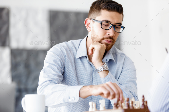Portrait of two young man playing chess - Stock Photo - Images