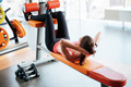 Beutiful woman athlete doing abdominal crunches on bench in gym