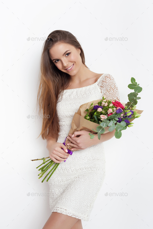 Young cute woman holding bunch of flowers - Stock Photo - Images