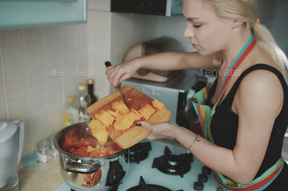 Young woman preparing pumpkin soup - Stock Photo - Images
