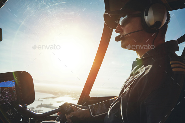 Pilot flying a helicopter on a sunny day - Stock Photo - Images