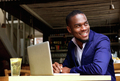 Smiling black businessman with laptop at cafe - PhotoDune Item for Sale