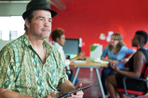 Confident male designer working on a digital tablet in red creative office space - Stock Photo - Images