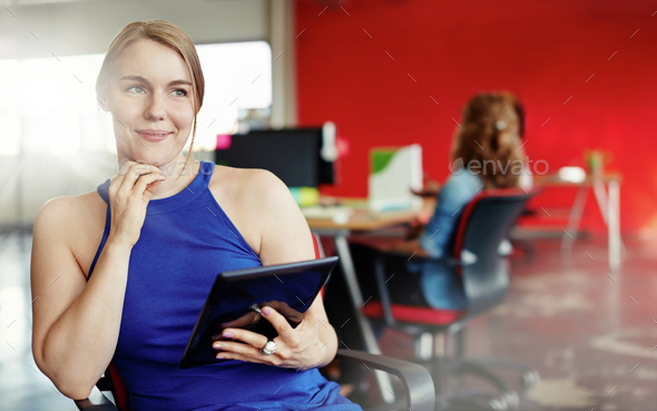 Confident female designer working on a digital tablet in red creative office space - Stock Photo - Images