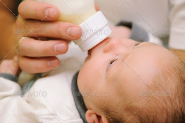 Dad feeding his baby - Stock Photo - Images