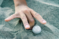hand of a child playing with marbles in the sand - PhotoDune Item for Sale
