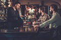 Cheerful old friends drinking draft beer at bar counter in pub. - PhotoDune Item for Sale