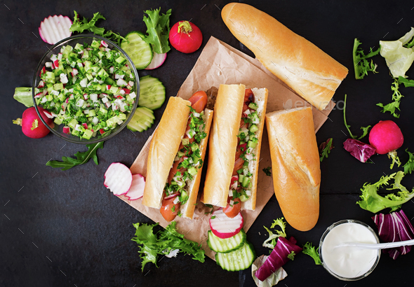 Healthy Hot Dog dressed with yogurt and cucumber salsa with radishes on dark backgroud. Top view - Stock Photo - Images