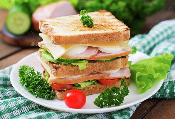 Club sandwich with cheese, cucumber, tomato, ham and eggs. - Stock Photo - Images